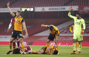 Players call for medical help after a head clash between Arsenal's David Luiz and Raul Jimenez of Wolves.