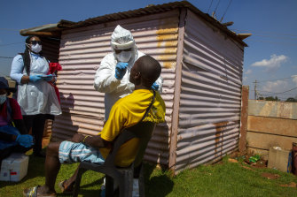 Health workers collects samples for coronavirus testing outside a shack to combat the spread of COVID-19 at Lenasia South, South Johannesburg, South Africa.