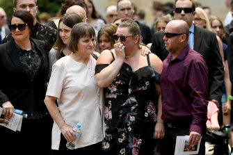 Mourners are seen embracing during a memorial service for White Island volcano victims Anthony, Elizabeth and Winona Langford at Maris College North Shore Auditorium in Sydney.