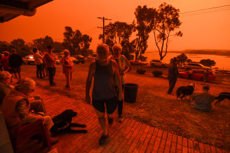 Residents gather as fire turns the skies over Mallacoota red on January 4, 2020.