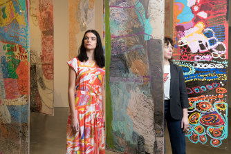 Lisa Gorman with model, Domanique Hutchins, wearing a dress with artwork from Mangkaja Artists, and surrounded by their artwork in the Museum of Contemporary Art in Sydney.