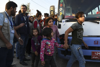 A group of Syrians disembarks from one of the buses that brought hundreds of displaced Syrians to the Bardarash refugee camp in Iraqi Kurdistan.