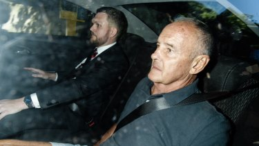 Chris Dawson is driven to Surry Hills police station on Thursday morning, accompanied by Detective Senior Constable Daniel Poole.