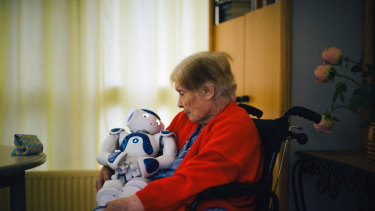 A patient sits with Zora at the Jouarre nursing facility outside Paris.