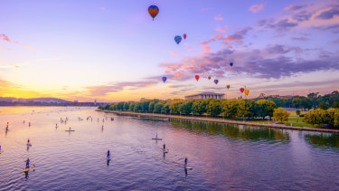Balloons above the National Library as the sun rises over Lake Burley Griffin while paddle boarders take to the water.