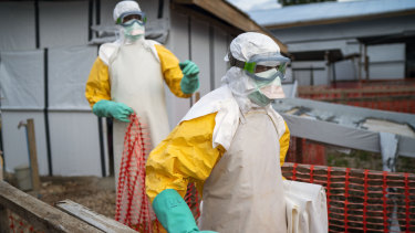 Health workers wearing protective suits take their shift at a treatment centre in Beni, Congo.