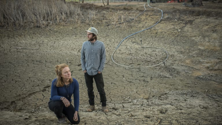 Erika Watson and Hayden Druce, owners of Epicurean Harvest, in a dried-out dam on their property in Hartley.