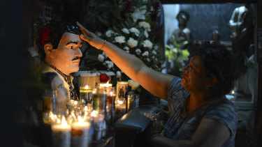 A woman prays to the folk saint Jesus Malverde in Culiacan, the capital of Sinaloa state in Mexico.