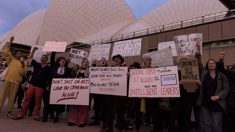 Protesters on the harbour foreshore opposing the projection of promotional material onto the Opera House sails.