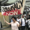 A woman holds a banner to demand full democracy in Hong Kong.
