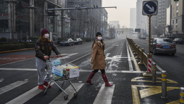 A couple cross the road in a deserved Beijing. The coronavirus has hit demand for products from Australian companies in their key export market.