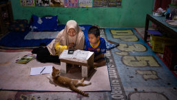 Syaiful, 12, who can't freely move his lower body or right hand, studies at home with his mother Nurhidayah in Banyumas, Central Java.