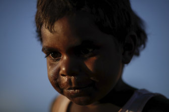 A boy waits for performances to start during a community event to celebrate to closure of the Uluru.
