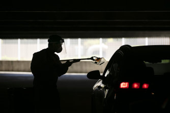 A healthcare worker uses a grabber to collect a nasal swab sample at a COVID-19 drive-through testing site in California.