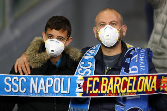 Fans were face masks at the Champions League match between Napoli and Barcelona in Italy.