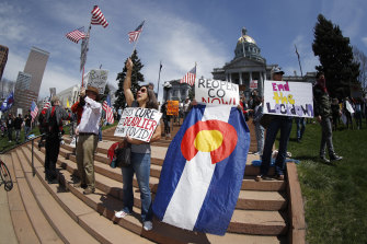 Protesters wave placards and flags as they stand on the west steps of the State Capitol during a protest against the stay-at-home order issued by Colorado Governor Jared Polis.