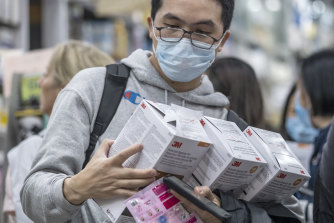 A customer inspects respirators at a pharmacy in the Central district of Hong Kong.