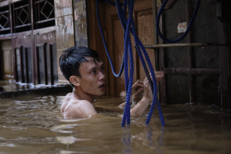 A man tries to access his house in a flooded neighbourhood of Jakarta in January, when 17 people were killed.