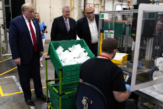 President Donald Trump watches masks being made as he participates in a tour of a Honeywell International plant.