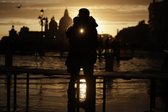 A couple watches the sun set over a flooded Venice following a 1.5-metre tide.