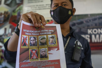 A police officer shows a wanted poster displaying the photos of two militants Ali Kalora, top left, and Jaka Ramadan, bottom left, who were killed during a shootout with security forces.