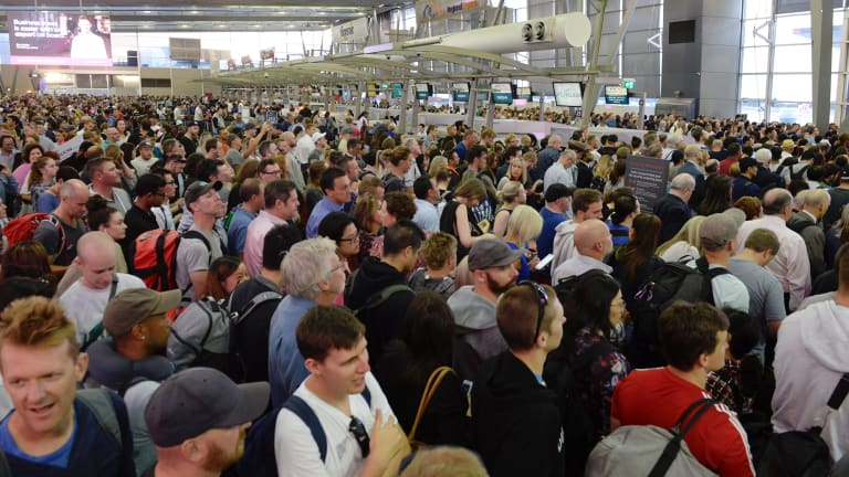 Passengers at thedomestic terminal wait to go through security after technical issues effectively shut down the airport on Friday morning.