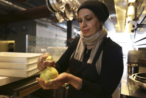 Muna Anaee prepares a ball of khobz orouk, a flatbread from her native Iraq, at the Tawla restaurant kitchen in San Francisco.