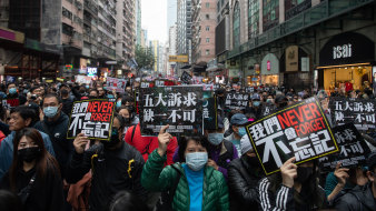 Demonstrators hold signs during a protest in the Causeway Bay district of Hong Kong.
