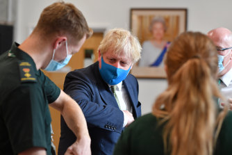 Boris Johnson, seen here visiting paramedics, is expected to announce a ban on Huawei equipment in Britain's 5G networks.