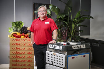 """Coles chief Steven Cain with one of the """"daleks"""" that will pick online grocery orders."""