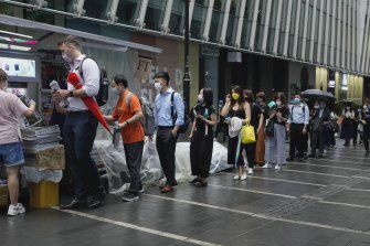 Customers queue up for last issue of Apple Daily at a newspaper booth at a downtown street in Hong Kong on Thursday.