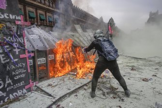 A demonstrator throws burning petrol at a police shield wall during a march to commemorate International Women's Day in Mexico City on Monday, March 8.