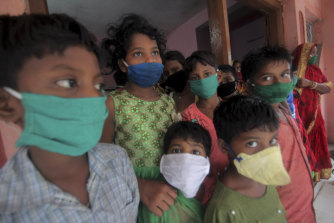 Evacuated children wearing masks as a precaution against the spread of coronavirus stand at a relief camp.