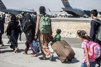 Evacuees walk towards their flight at Kabul airport.