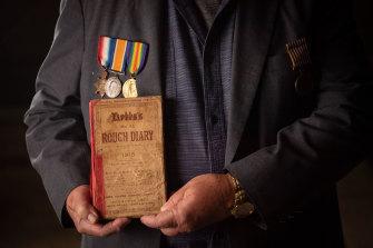 Malcolm Milliken holds his uncle Morris Milliken's World War I diary.