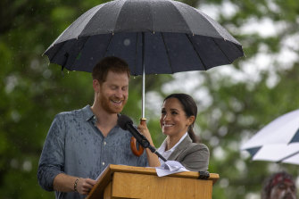 Dream team: Meghan shelters Prince Harry while he speaks at a community picnic in Dubbo.