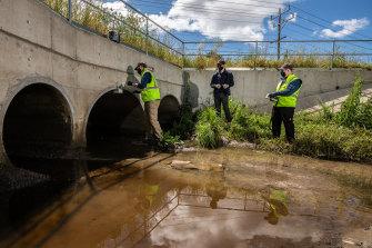 EPA scientist Simon Sharp and consultants from Bio2Lab install pollution sensors in Merlynston Creek.