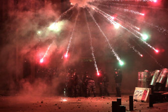 Protesters shoot fireworks towards riot police on a road that lead's to Lebanon's Parliament.