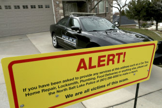 The warning sign and a police officer's vehicle at the victim's home in North Salt Lake, Utah., after plumbers, prostitutes and others were sent to the address.