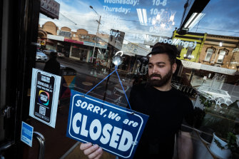 Mas Azemi of Mas Barber Shop in Brunswick closes his shop in August. Many Melbourne businesses remain shut under lockdown restrictions.