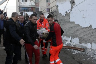 Rescuers carry an injured woman after a magnitude 6.4 earthquake in Thumane, western Albania.