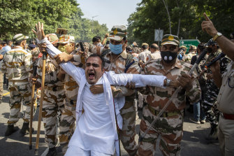A man is detained by soldiers in New Delhi during widespread protests across India.
