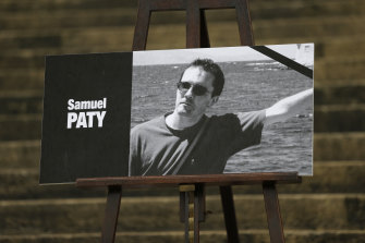 The portrait of slain teacher Samuel Paty is displayed on the steps of the National Assembly in Paris.