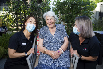 Aviation industry workers Mitsu Kamo (left) and Louise Mathers, with Regis Aged Care resident Jean Sarsby, have been hired  under a new program to help organise visits for nursing home residents.