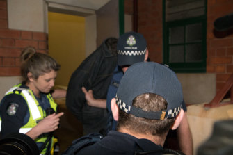 Police with Adrian Basham outside Bairnsdale Magistrates Court last year.
