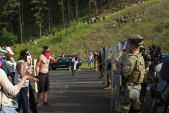 Protesters clash with a line of law enforcement officers in Keystone, SD, on the road leading to Mount Rushmore.