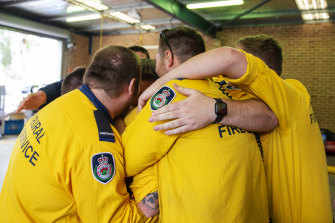 Members of the Horsley Park Rural Fire Brigade embrace while remembering their fallen comrades on Sunday.