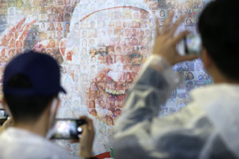 People observe a wall painting depicting Pope Francis at Nagasaki Prefectural Baseball Stadium.