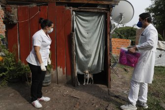 Two health workers wait for the occupant of a shack to come out to be tested for COVID-19 in Limpio, Paraguay.