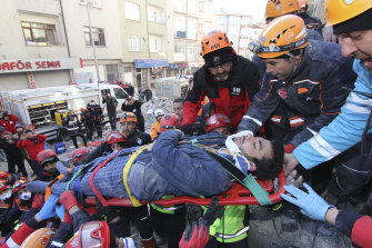 Rescue workers on Saturday carry a wounded man who was found alive in the rubble of a building destroyed by Friday's earthquake in Elazig, eastern Turkey.